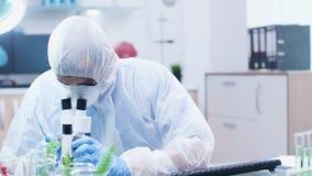 Kemist som bär en overall som ser ett mikroskop stock video