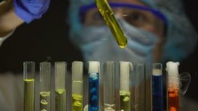 Kemist som kontrollerar bottensats i rör med gul flytande, vikter som sänder ut rök stock video