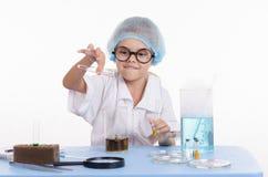 Kemisten häller flytande från provröret in i en flaska Royaltyfri Bild