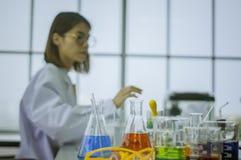 Kemister arbetar labbet i morgon, med provstycken som arbetar med färgrika vätskekemikalieer, Glass rör, för skönhetsmedel, framk royaltyfri fotografi