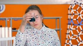 Kemistskolaflicka 10-11 år i exponeringsglas som blandar kemikalieer i provrör arkivfilmer