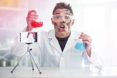 Kemistudentkänsla som är skandalös efter mislyckat kemiexperiment arkivbild