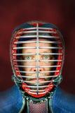 Kendo - κλείστε επάνω το πορτρέτο του kendoka με το κράνος Στούντιο που πυροβολείται με το κόκκινο υπόβαθρο Στοκ εικόνα με δικαίωμα ελεύθερης χρήσης