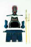 Kendo - τεθωρακισμένο και εξοπλισμός Kendoka που τακτοποιούνται και που επιδεικνύονται στο άσπρο υπόβαθρο, με το shinai και το ξύ Στοκ Εικόνες