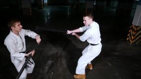 Kendo del entrenamiento de dos hombres en un estacionamiento El hombre mantiene apagado un ataque de la espada almacen de metraje de vídeo
