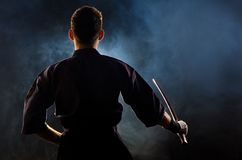 Kendo expert ready for fight. Kendo fighter with bokken. dark background with smoke and dynamic light Stock Photography