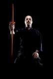 Kendo fighter. Portrait of a kendo fighter with bokken, against black backgroung Stock Photo