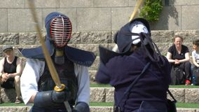 Kendo fighters practice fighting with a bamboo sword shinai in a city park. stock video footage