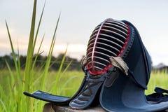 Kendo Helmet ou homens usados e sujos no campo de grama no fundo do por do sol Imagem de Stock