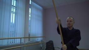 Kendo Trains principal dans le Hall avec un bâton en bois exécute un Kata banque de vidéos
