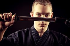 Kendo warior. Handsome young man practicing kendo. Over dark background Royalty Free Stock Images