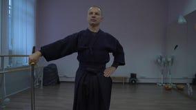 Kendoka entrena con la espada en el pasillo de deportes, afila con piedra su maestría almacen de video