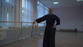 Kendoka s'exerce avec l'épée, dans la salle de gymnastique les vacances de Halloween banque de vidéos