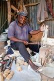 KENIA, AFRIKA - 10. DEZEMBER: Ein Mann, der Abbildungen im Holz schnitzt. Lizenzfreie Stockbilder