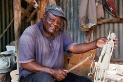 KENIA, AFRIKA - 10. DEZEMBER: Ein Mann, der Abbildungen im Holz schnitzt. Lizenzfreies Stockfoto