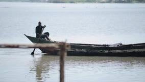 KENIA, KISUMU - 20 DE MAYO DE 2017: Hombre africano joven, pescador que se sienta en el barco solamente y que rema en el mar metrajes