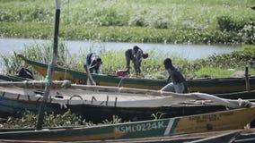 KENIA, KISUMU - 20 DE MAYO DE 2017: Hombre africano joven que prepara su barco antes de trabajo Gente que toma la ducha en el lag almacen de metraje de vídeo