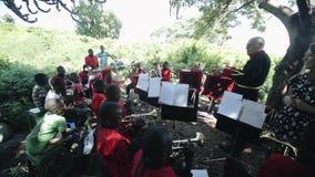 KENIA, KISUMU - 20 DE MAYO DE 2017: La cámara se baja Concierto de una banda africana con un dreyer caucásico en el aire abierto almacen de metraje de vídeo