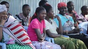 KENIA, KISUMU - 20 DE MAYO DE 2017: Mujeres del maasai africano local de la tribu que se sienta en las sillas y que mira en algun almacen de video