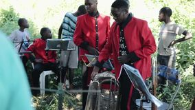 KENIA, KISUMU - 20 MEI, 2017: De muzikale groep speelt buiten De Afrikaanse mensen, mensen in rode jasjes treffen te tonen voorbe stock video