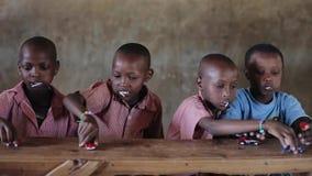 KENIA, KISUMU - 20 MEI, 2017: Kale mooie Afrikaanse jongens die bij de lijst zitten en met speelgoed, auto's spelen stock footage