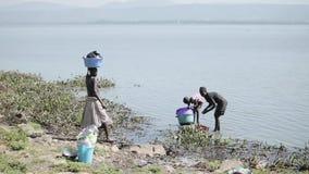 KENJA KISUMU, MAJ, - 20, 2017: Kobieta i jej córki obmycia naczynia w jeziorze, dziewczyna niesiemy basen z odziewamy na głowie zbiory