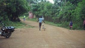 KENJA KISUMU, MAJ, - 20, 2017: Tylny widok chłopiec odprowadzenie przez drogi w Afryka Samiec z rowerowym odprowadzeniem w lesie obrazy royalty free