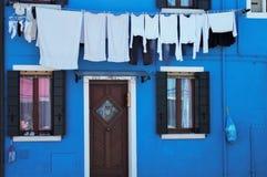 Kenmerkend blauw gekleurd huis in Burano, Venetië Italië Voorgevel van huis met het hangen van kleren stock foto's