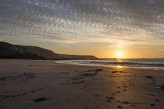 Kennack piaski wyrzucać na brzeg przy wschodem słońca z piaskowatą plażą i pięknym chmurnym niebem, Cornwall, UK zdjęcie royalty free