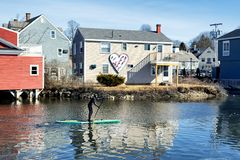 Kennebunkport Maine Winter Batson River. An active person on a paddleboat in the Batson River during wintertime in Kennebunkport Maine on a sunny cold day stock photography