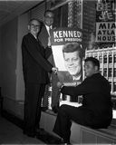 Kennedy Campaign supporters. Three John F. Kennedy campaign supporters hang Kennedy campaign posters out of building windows in 1960. (Image taken from B&W Stock Photo