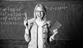 Kennisproces om kennis door gedachten te verwerven De vrouwenleraar met boek voor bord denkt over stock afbeeldingen