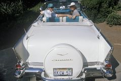 Kenny Kragen and wife in a white 1957 Chevrolet in a Beverly Hills Car Show in Los Angeles, CA Royalty Free Stock Image
