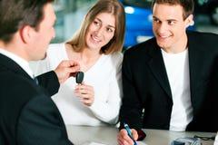 Kennzeichnender Kaufvertrag der Paare am Autohändler Stockfotografie