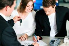 Kennzeichnender Kaufvertrag der Paare am Autohändler Stockbild