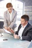 Kennzeichnender Vertrag des schönen Chefs am Schreibtisch Stockbilder
