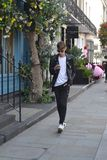 Keno Eckert-Ludwig during London Fashion Week. Keno Eckert-Ludwig on his phone in Belgravia, London wearing Gucci Ace Sneakers and Tom Ford sunglasses royalty free stock photos