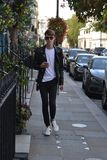Keno Eckert-Ludwig during London Fashion Week. On his phone in Belgravia, London wearing Gucci Ace Sneakers and Tom Ford sunglasses stock image