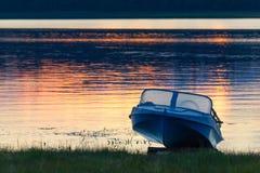 Kenozersky国家公园,俄罗斯 一艘老蓝色铝汽艇叫`在湖岸的Kazanka `在日落 在的蓝色小船 库存图片
