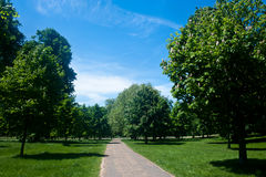 Kensington Gardens in London. Tranquil pathway surrounded by luxuriant vegetation and trees in Kensington Gardens, Hyde Park, London Royalty Free Stock Photography