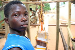 African boy in his outdoor cloth weaving shop  Stock Photo