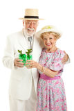 Celebrating Kentucky Derby Day. Kentucky Colonel and his wife dressed up and drinking mint juleps in celebration of Kentucky Derby Day. Isolated on white royalty free stock photos