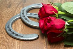 Kentucky Derby Red Roses with Horseshoes on Wood. Red Roses - official flower of the Kentucky Derby with cast iron horseshoes on wood planks royalty free stock images