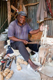 KENYA, ÁFRICA - 10 DE DEZEMBRO: Um homem que cinzela figuras na madeira. Imagens de Stock Royalty Free
