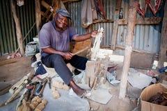 KENYA, ÁFRICA - 10 DE DEZEMBRO: Um homem que cinzela figuras na madeira. Fotos de Stock