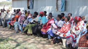 KENYA KISUMU - MAJ 20, 2017: Folk från lokalt afrikanskt stammaasaisammanträde på stolarna och att se någonstans stock video