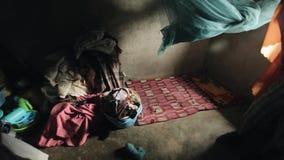 KENYA KISUMU - MAJ 20, 2017: Inom ett fattigt litet hus i Afrika Mycket kläder, linne ligger på det konkreta golvet lager videofilmer