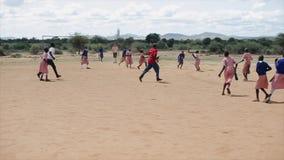 KENYA KISUMU - MAJ 20, 2017: Lyckliga afrikanska barn och Caucasian folk som utanför spelar fotboll tillsammans lager videofilmer