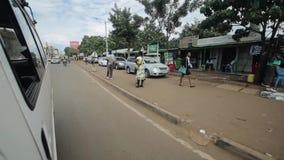 KENYA KISUMU - MAJ 20, 2017: Sikt till och med vindrutan från inre en bil Bilen rider till och med staden i Afrika arkivfilmer