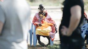 KENYA, KISUMU - MAY 20, 2017: African woman from local maasai tribe sitting on chair and hold balloon. royalty free stock image